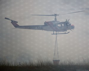 The helicopter rises from loading at the pond, shrouded by smoke.
