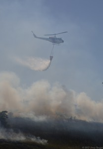 The chopper drops a load of water directly upslope from firefighters.