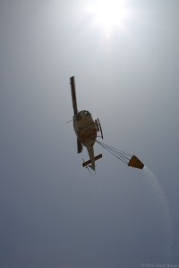 The fire helicopter passes directly overhead after releasing a load.